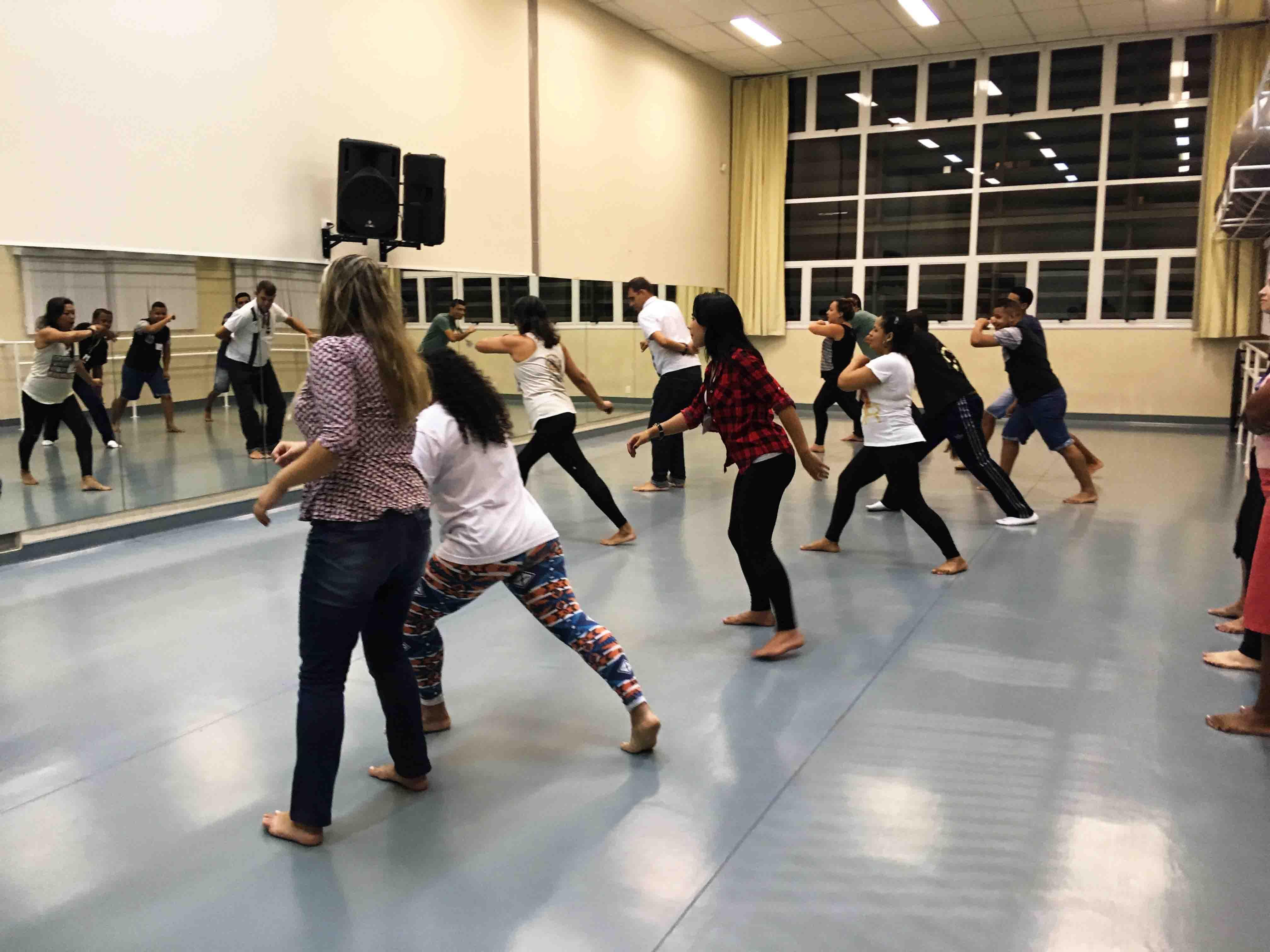 Em frente a espelho, turma treina movimentos de capoeira guiados por professor. Fim da descrição.