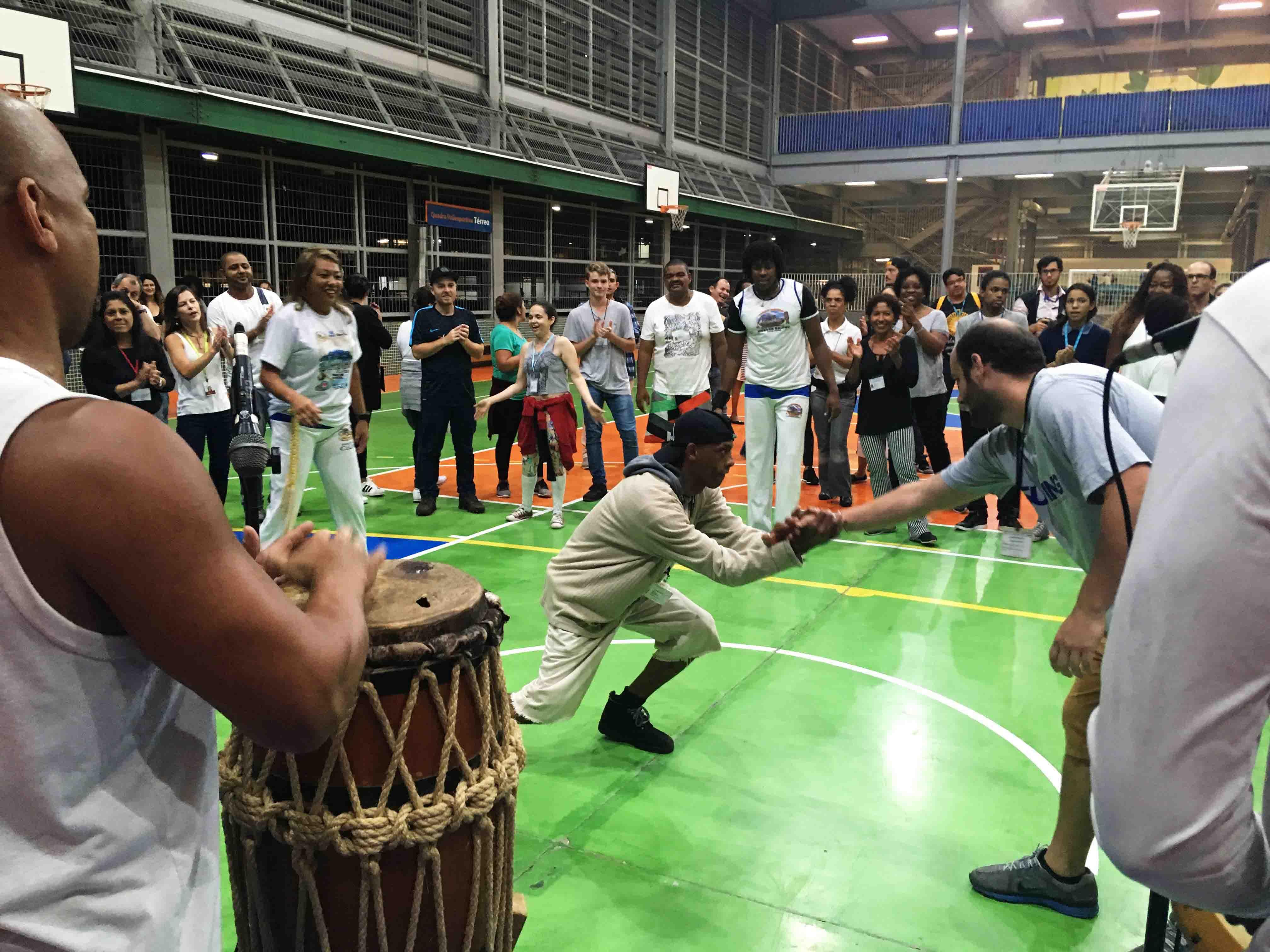 Em roda de capoeira, dois jogadores se cumprimentam ao centro. Um deles está levemente curvado e segura com as duas mãos o braço do outro jogador. Em volta, os outros estudantes observam. Em primeiro plano, homem toca atabaque. Fim da descrição.