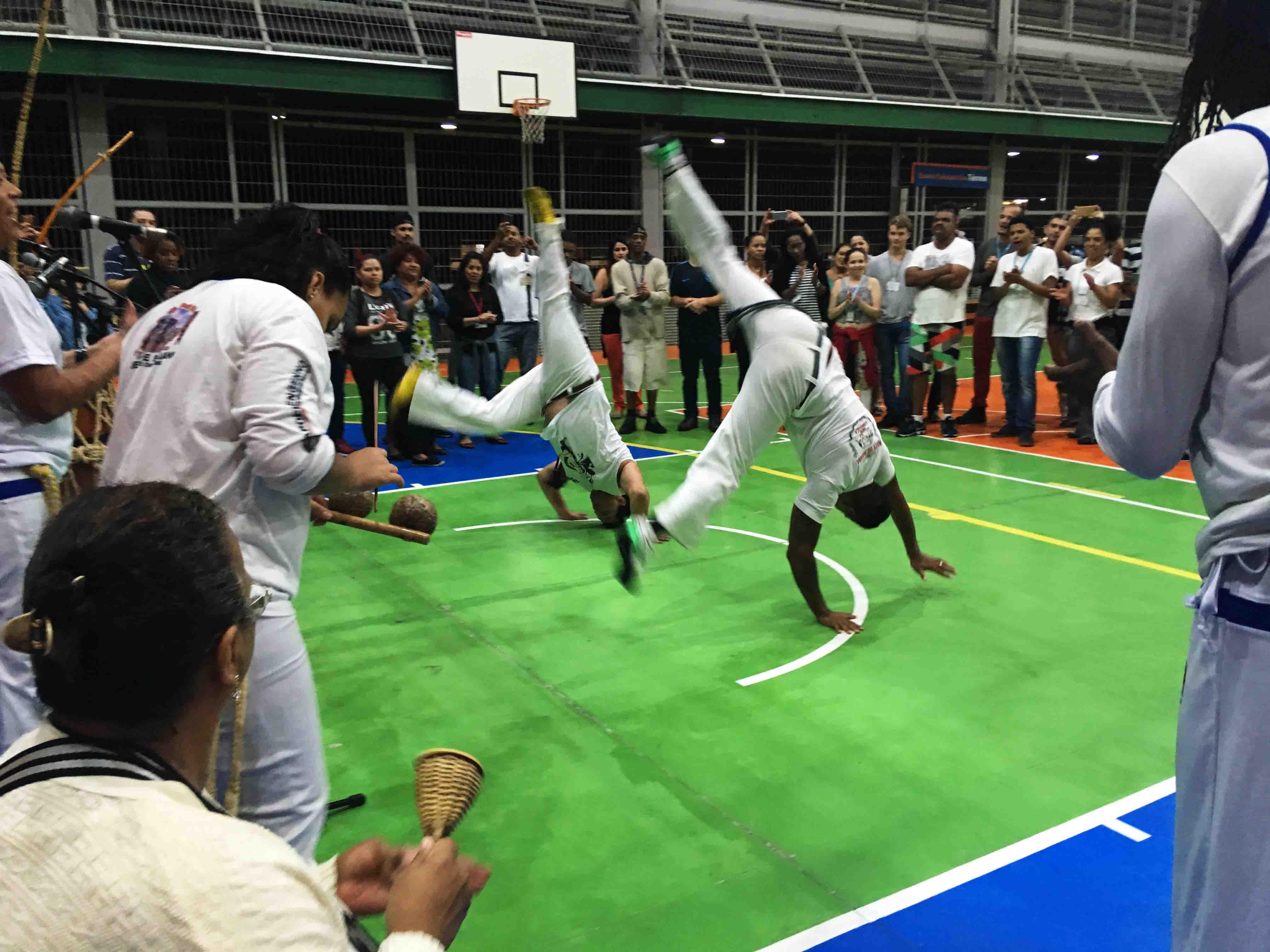 """Em roda de capoeira, dois jogadores realizam movimento de """"estrela"""" enquanto são observados pelo resto da turma, que toca instrumentos e bate palmas. Fim da descrição."""