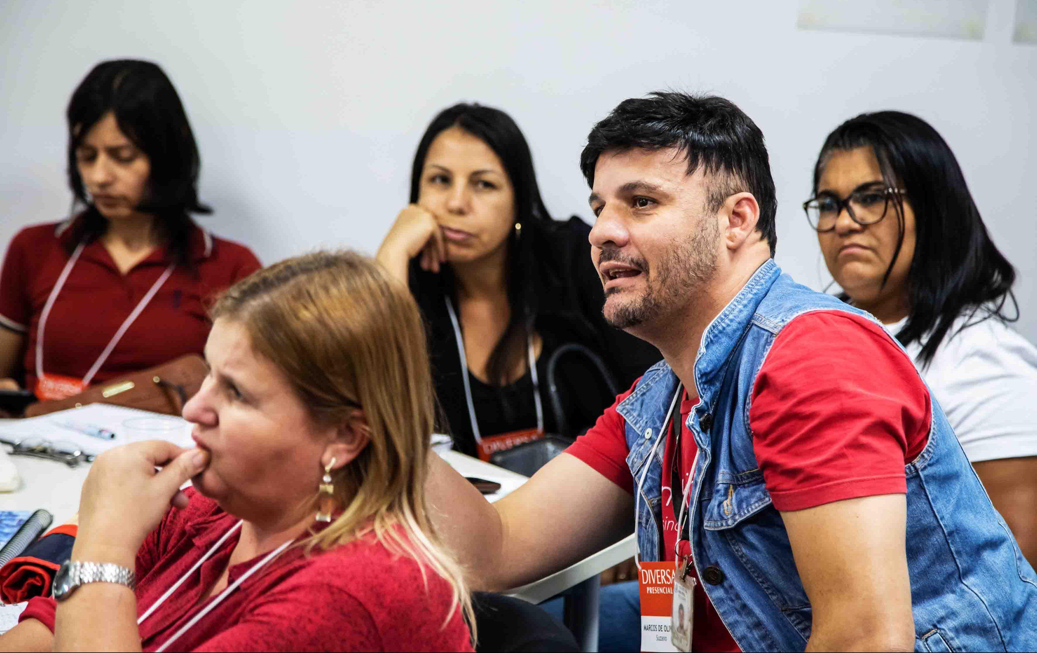 """Educadores de Suzano sentados em carteiras olham para frente concentrados. Eles vestem crachás com os dizeres """"DIVERSA presencial"""". Fim da descrição."""