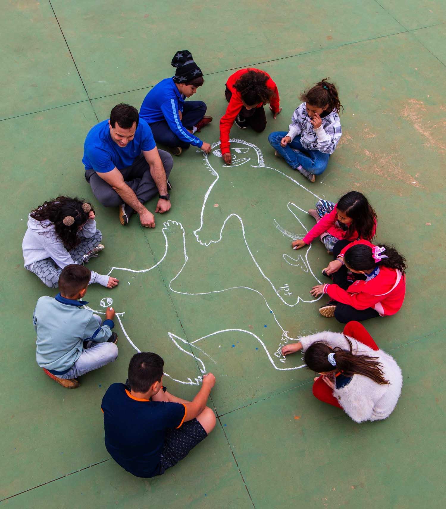 Imagem aérea do professor Luiz Gustavo e sua turma desenhando corpos no chão da quadra poliesportiva, usando giz. Fim da descrição.