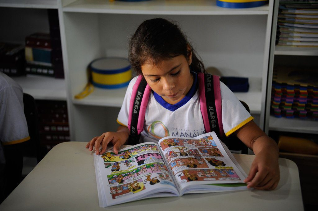 Sentada em carteira escolar e com a mochila nas costas, aluna lê história em quadrinhos. Fim da descrição.