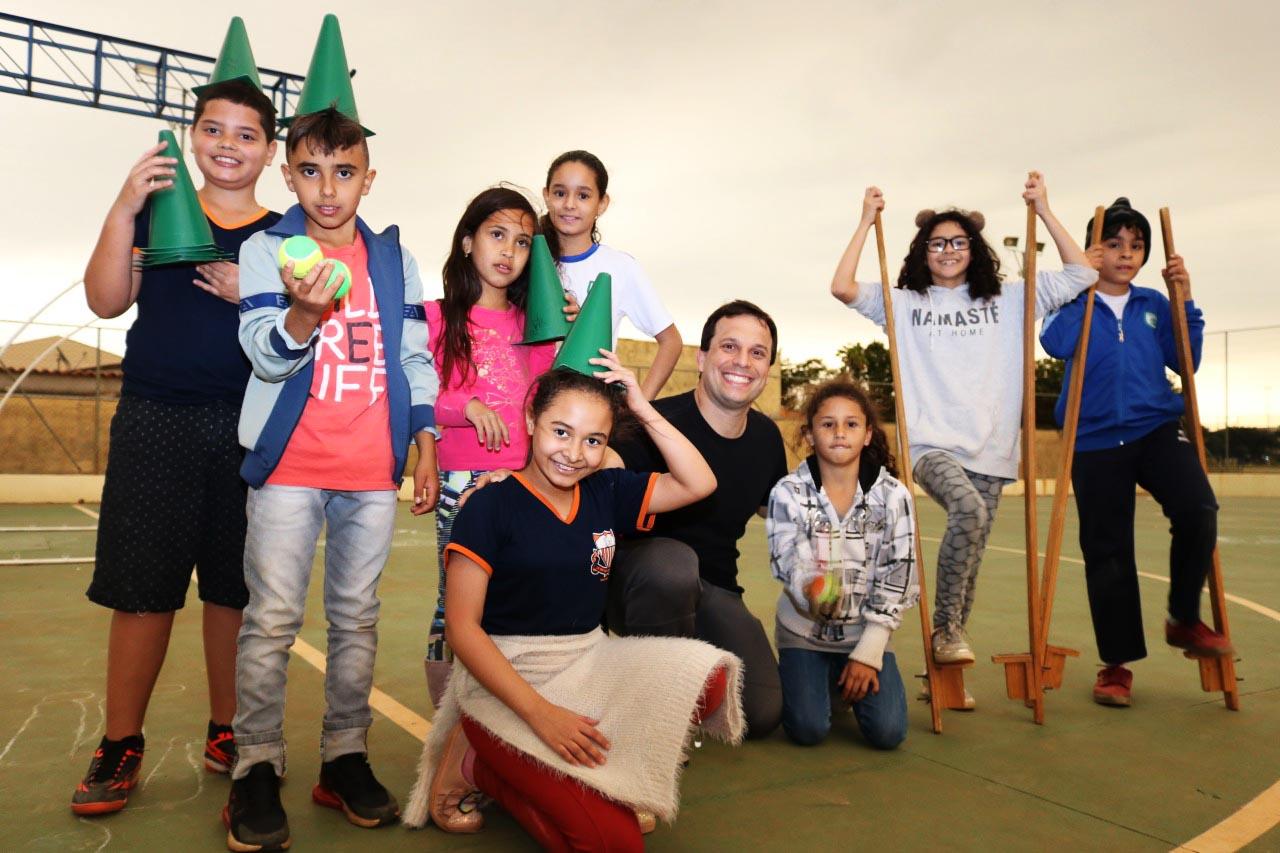 O professor Luiz Gustavo posa com seus estudantes. O grupo sorri. Alguns usam chapéus e pernas de pau. Fim da descrição.