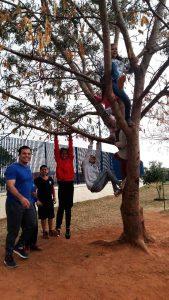 O professor Luiz Gustavo posa para foto com estudantes ao lado de árvore. Os alunos estão escalando a árvore, pendurados no tronco. Fim da descrição.