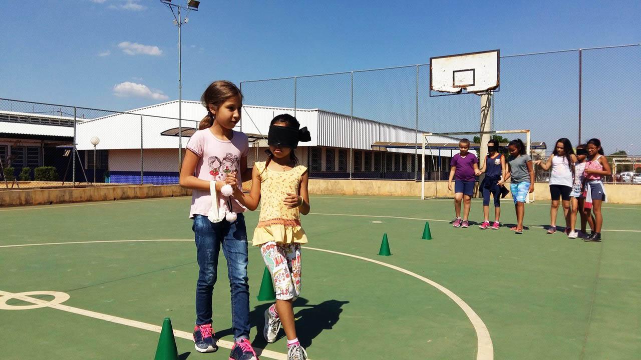 Em quadra poliesportiva, estudantes realizam atividade sensorial, em que um estudante usa vendas enquanto outro o guia pela quadra. Alguns cones estão dispostos no chão. Fim da descrição.