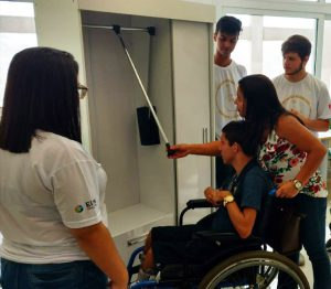 Jovem com deficiência física observa guarda-roupa adaptado juntamente a mulher que segura sua cadeira de rodas. Ao lado, três estudantes assistem. Fim da descrição.