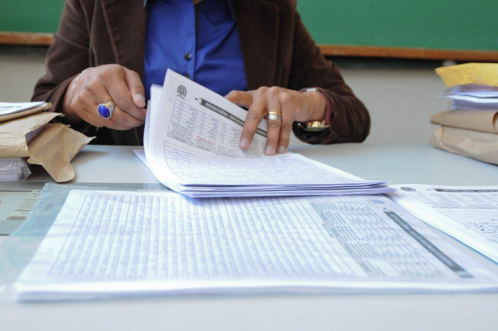 Mulher examina diversos documentos em uma mesa. A imagem focaliza as suas mãos, e seu rosto não aparece. Fim da descrição.