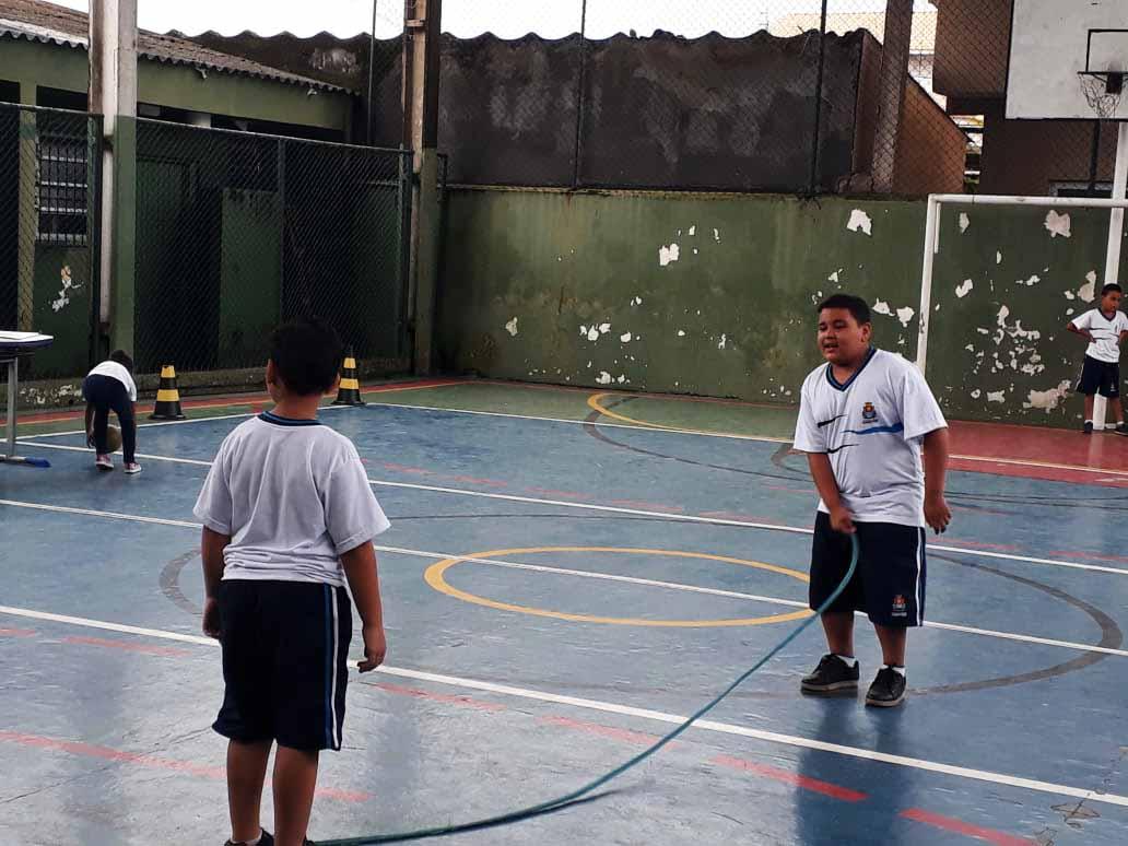 Em quadra poliesportiva de escola, dois estudantes aparecem pulando corda. Um deles está segurando a corda com a mão direita. Ambos usam uniforme escolar. Fim da descrição.
