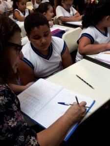 Em sala de aula, professora escreve em caderno depositado sobre carteira de Augusto, que está sentado e a observa. Fim da descrição.