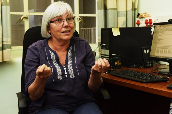 Em escritório, professora Judith Mckenzie fala enquanto gesticula com as mãos. Ela está sentada em cadeira ao lado de mesa de computador.