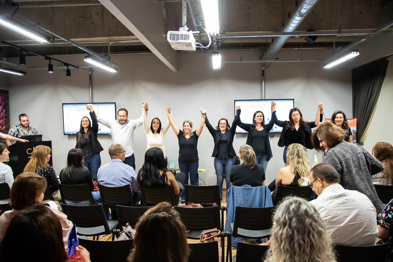 Em sala de reunião, educadores de São Roque estão de mãos dadas e erguidas. Eles estão de pé e de frente para uma plateia sentada em cadeiras. Fim da descrição.