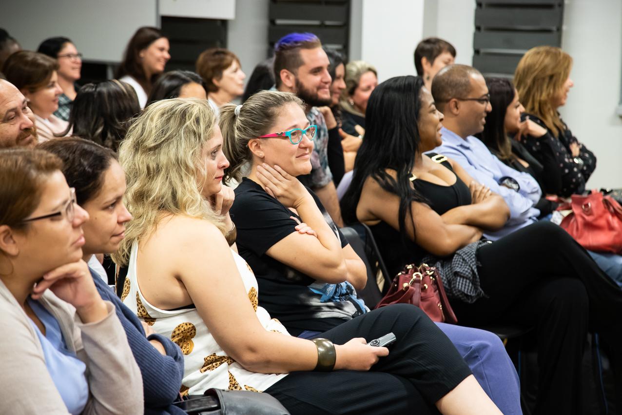 Em sala, educadores sentados em cadeiras olham atentos para a frente . Fim da descrição.
