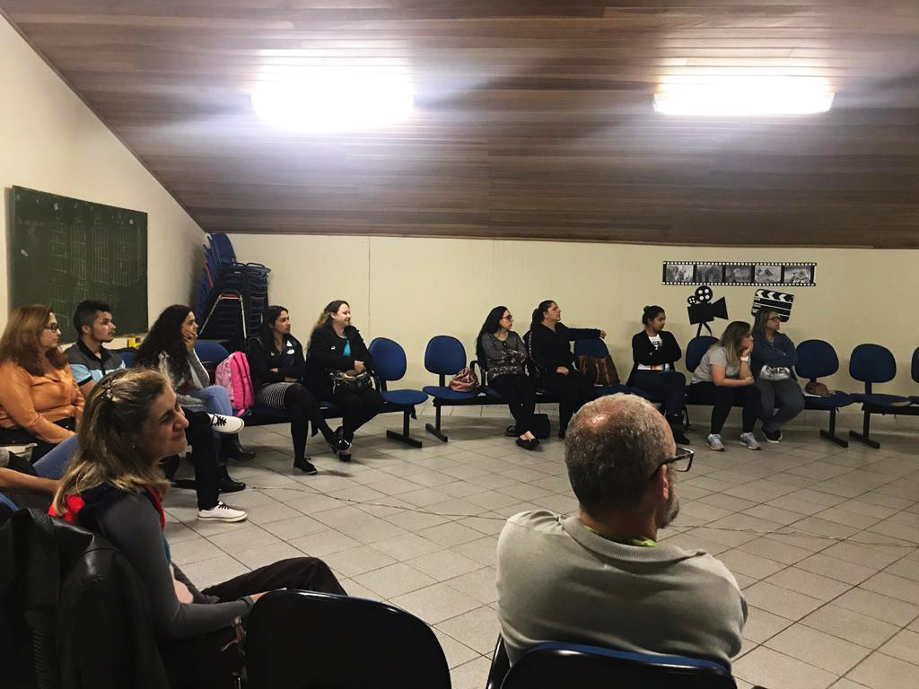 Em sala de reunião, educadores da escola EMEF Professora Maria José Ferraz Schoenacker estão sentados em cadeiras dispostas em roda. Fim da descrição.