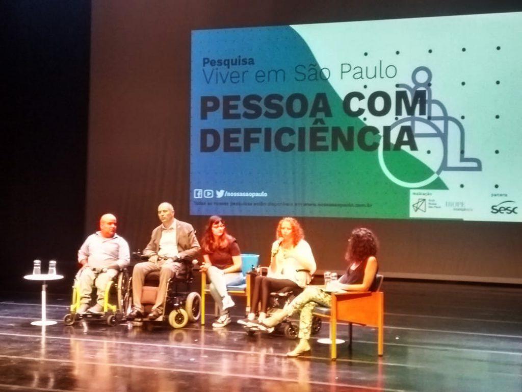 """Em palco, cinco pessoas estão sentadas lado a lado segurando microfone. Três delas estão em cadeiras de rodas. Do lado esquerdo, há uma mesa com dois copos de água. Ao fundo do palco, telão exibe capa  da pesquisa """"Viver em São Paulo: Pessoa com Deficiência"""". Fim da descrição."""