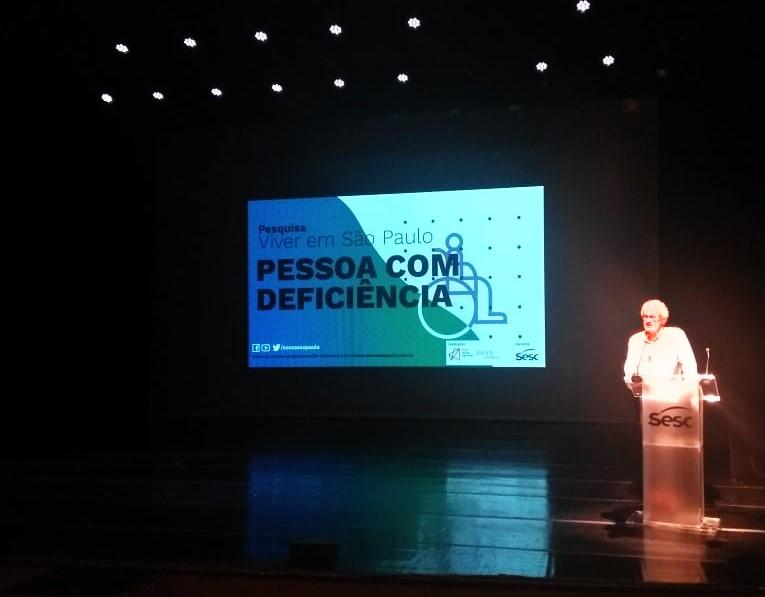 """Ao lado direito de palco, homem está em pé atrás de um púlpito com o logo do Sesc. Ao fundo do palco, telão exibe capa  da pesquisa """"Viver em São Paulo: Pessoa com Deficiência"""". Fim da descrição."""
