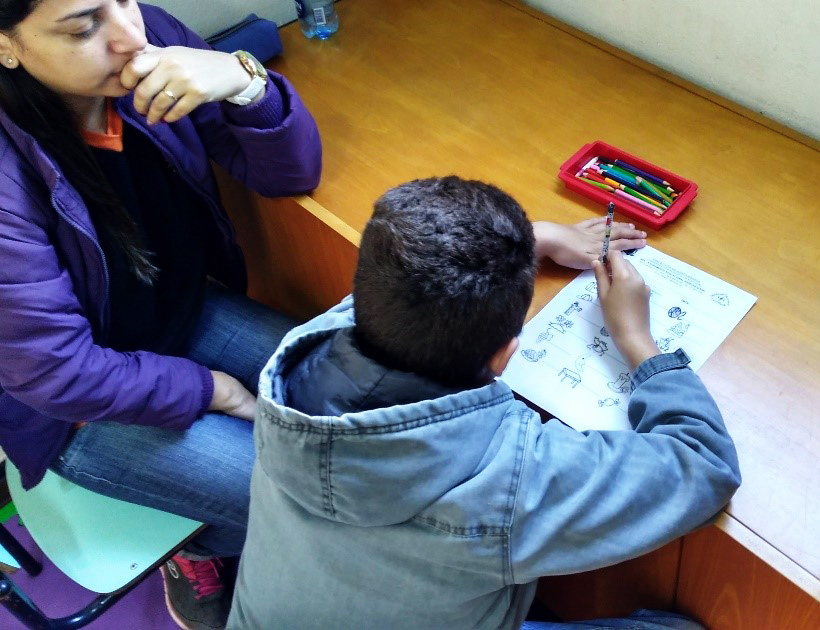 Professora e estudante sentam juntos. O aluno está apoiado na mesa com um lápis na mão, escrevendo em uma folha que tem algumas ilustrações. Há um estojo com diversos lápis de cor em cima da mesa. Fim da descrição.