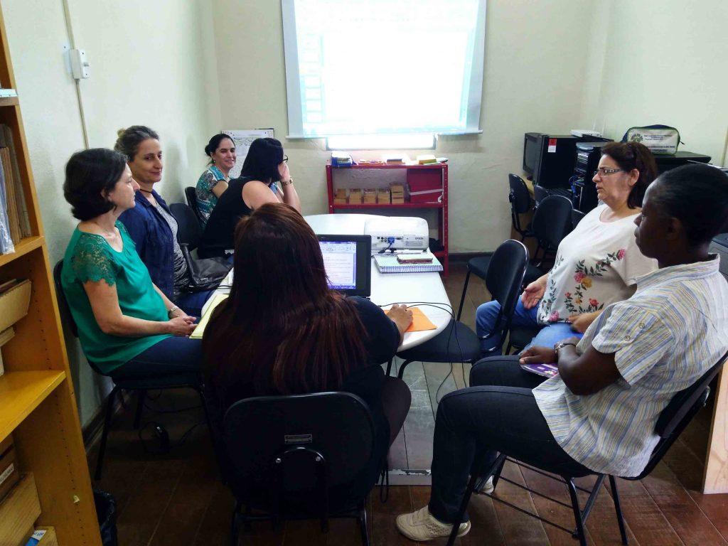 Sete pessoas se sentam reunidas em volta de uma mesa. Uma delas está em frente a um notebook e com a mão no mouse, e a imagem do computador está sendo projetada na parede. Fim da descrição.