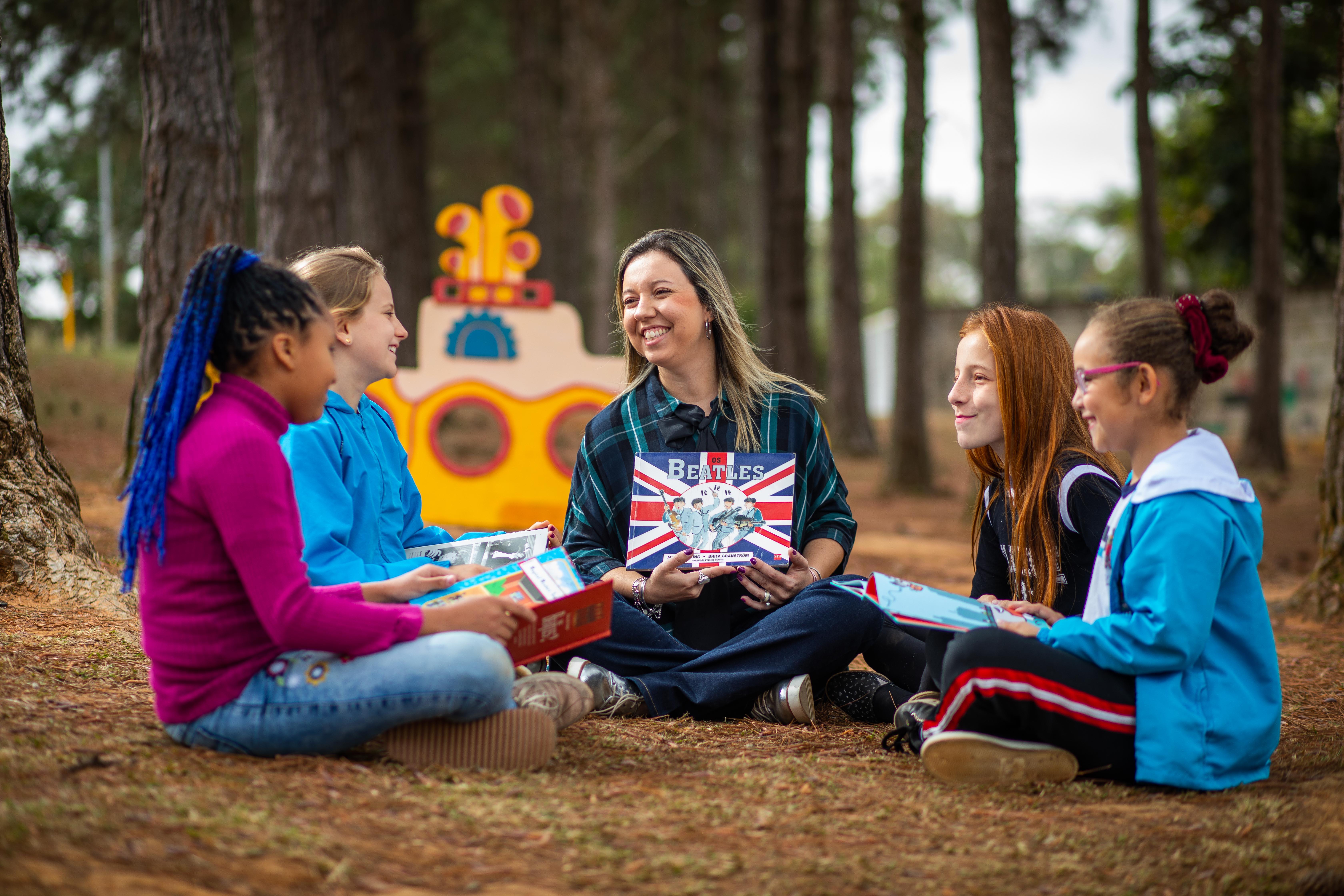 """Em espaço aberto e arborizado, professora Arabelle se senta em roda no chão com mais quatro alunos. Eles sorriem e seguram livros relacionados aos Beatles. Ao fundo, há um submarino amarelo, como o da música """"Yellow Submarine"""". Fim da descrição."""