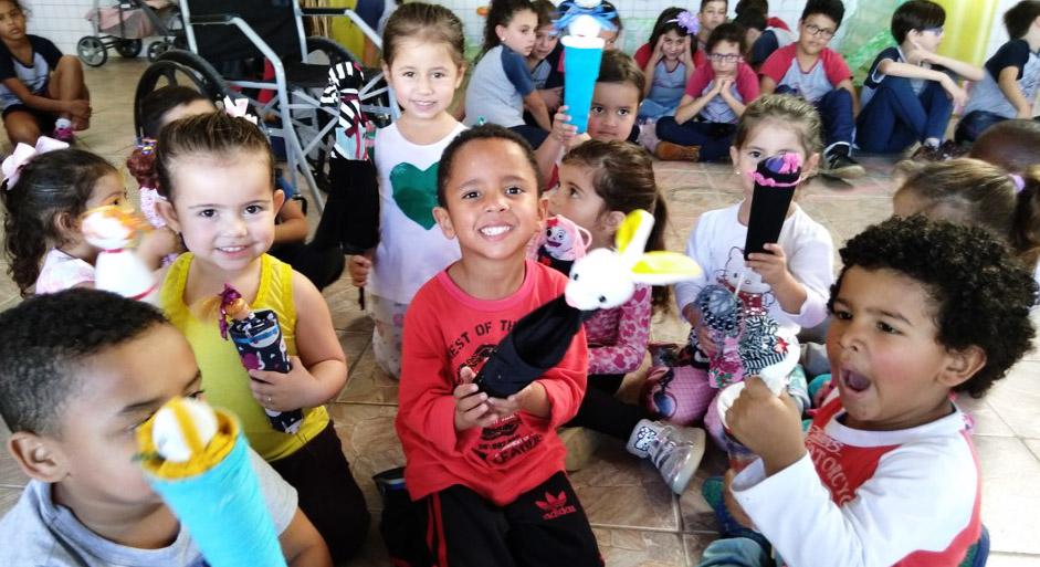 Crianças sorridentes sentadas no chão seguram bonecas abayomi produzidas por estudantes. Fim da descrição.