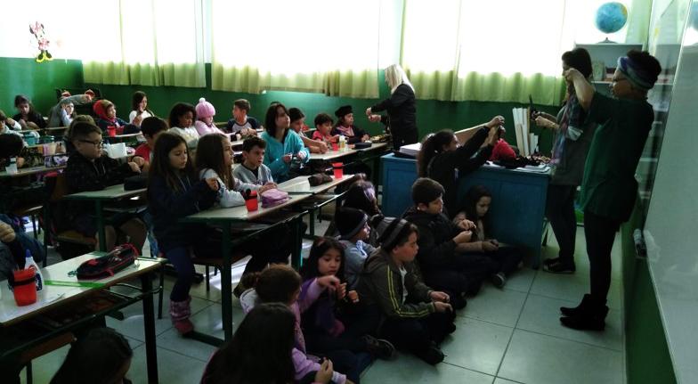 Em sala de aula, estudantes observam professora. Alguns estão sentados no chão, enquanto a maioria está em carteiras escolares. Fim da descrição.