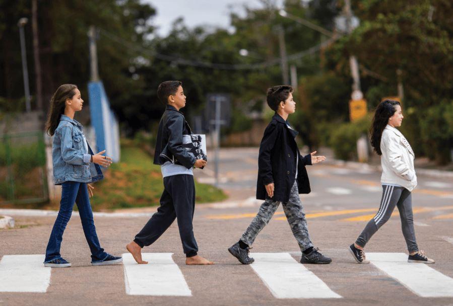 """Quatro estudantes atravessam faixa de pedestre, em referência à capa do álbum """"Abbey Road"""", dos Beatles. Fim da descrição."""