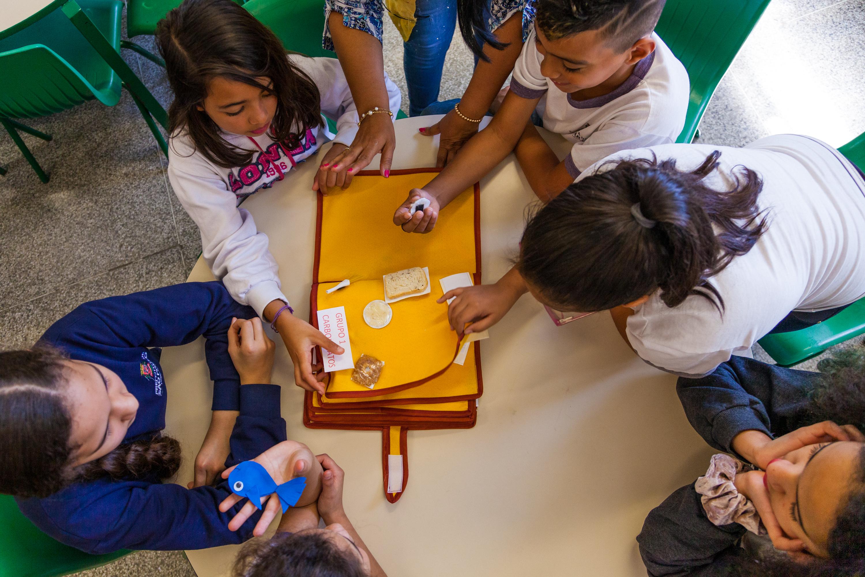Em sala de aula ao redor de uma mesa circular em imagem vista de cima, cinco estudantes e professora interagem com cadernode EVA com exemplos de alimentos de cada grupo e classe alimentar. Eles seguram algumas miniaturas de alimentos, como um peixe e uma fatia de pão. Fim da descrição.