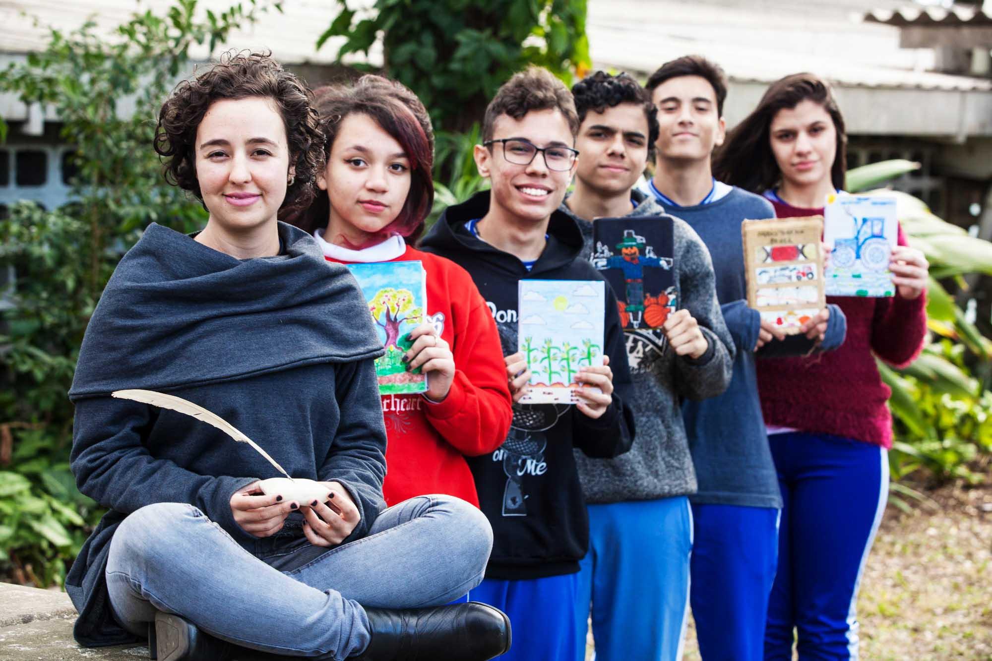 Em espaço arborizado, Mariana e seus estudantes posam para foto segurando seus cadernos de registros. Fim da descrição.