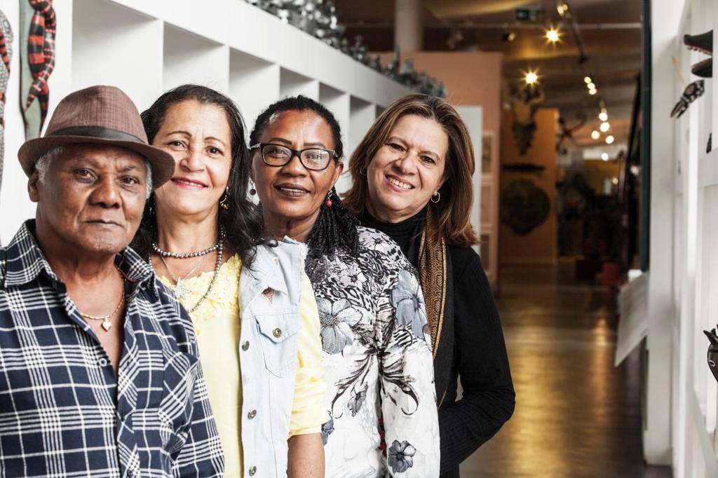 No museu Afro-Brasil, Nilma e três estudantes posam sorridentes para foto lado a lado. É possível ver algumas obras do museu atrás deles, todas com temática afro-brasileira. Fim da descrição.