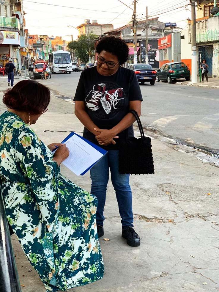 Sentada em ponto de ônibus, uma estudante segura um questionário de pesquisa. Ao seu lado, de pé, está uma mulher sorrindo e a observando. Ao fundo, vemos uma rua de um bairro de Osasco, com carros e ônibus passando. Fim da descrição.