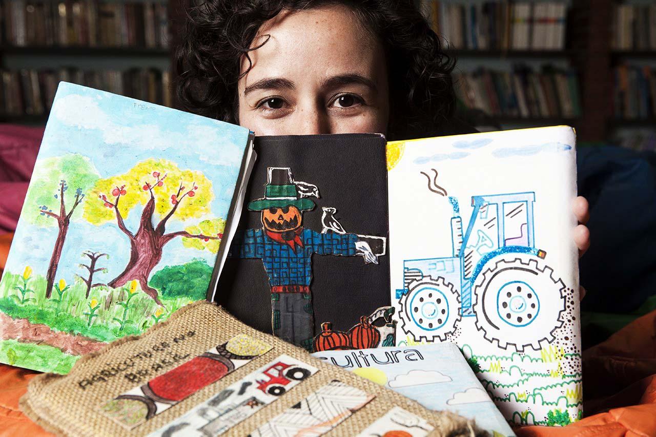 A educadora Mariana posa para foto com os cadernos de registro dos estudantes, que tem capas relacionadas à agricultura: uma plantação de milho, um espantalho e um trator. Fim da descrição.