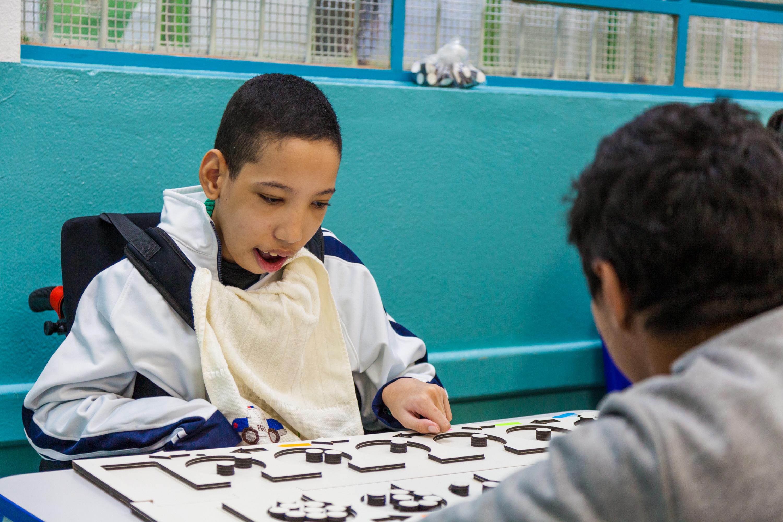 """O estudante Júnior utiliza o MPA """"Mancala"""" com um colega. Fim da descrição."""