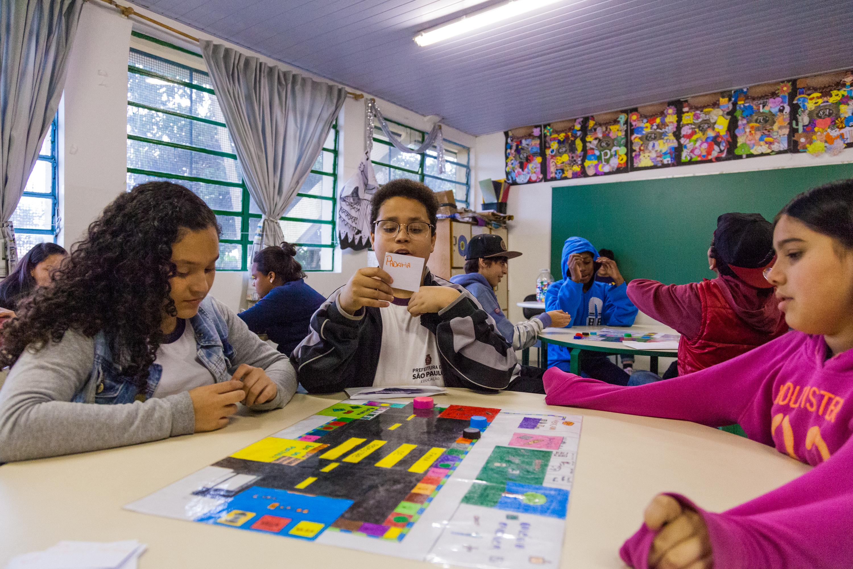 """Em sala de aula, três estudantes sorridentes interagem com versão simplificada do material pedagógico acessível """"Jogo do Território"""". Fim da descrição."""