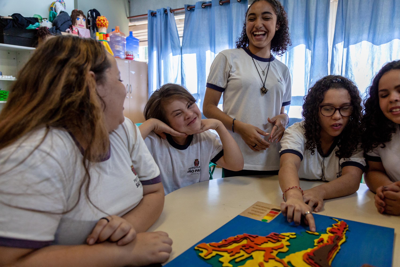 Em sala de aula, cinco estudantes interagem com material Mapa tátil. Três delas sorriem enquanto outras duas observam o material. Fim da descrição