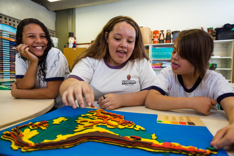 Em sala de aula, três estudantes interagem com mapa tátil em fase de finalização, pintado e com as camadas de relevo fixadas. Fim da descrição.