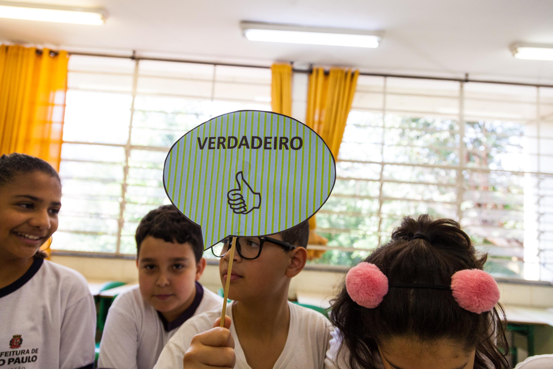 """Em sala de aula, estudante segura uma placa de papel que diz """"Verdadeiro"""", com a ilustração de um polegar para cima. Fim da descrição."""