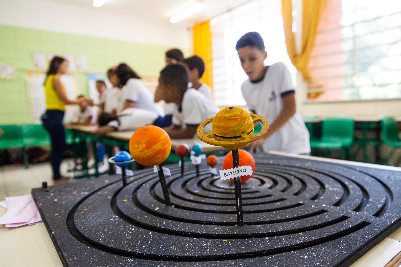 Em sala de aula, material pedagógico acessível está focado em primeiro plano. Ao fundo, estudantes estão apoiados em duas carteiras. Fim da descrição.