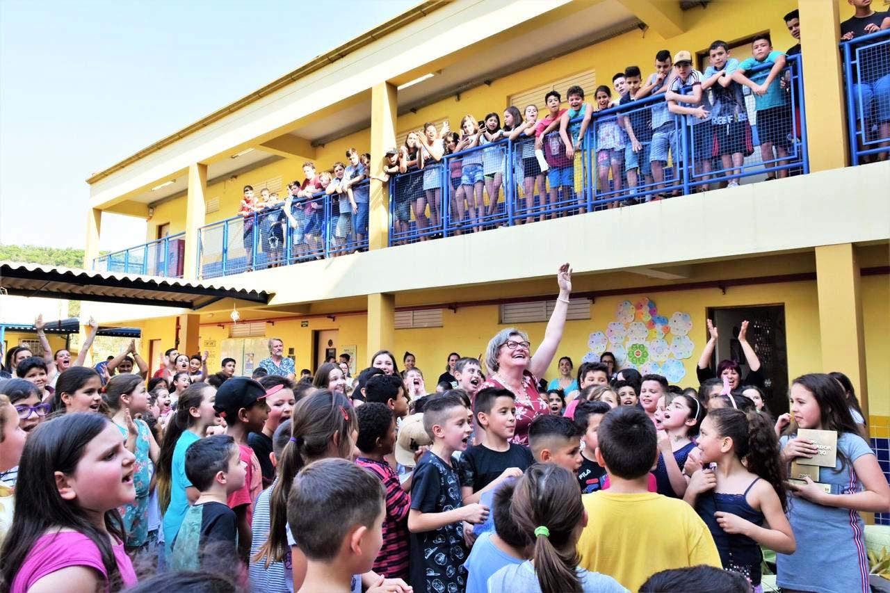 Em pátio de escola, Joice sorri e levanta o braço esquerdo, enquanto é rodeada por estudantes entusiasmados. Fim da descrição.