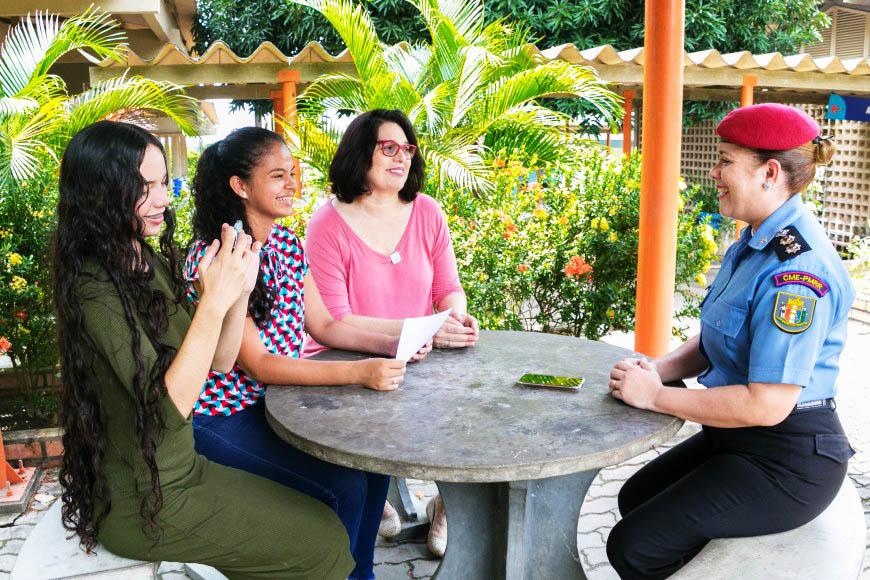 A professora Rutemara senta com duas alunas e com a Tenente Coronel PM Valdeane Alves em mesa redonda. As três se olham e sorriem. Fim da descrição.