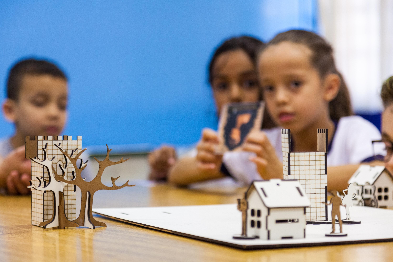 Em sala de aula, crianças sentadas em carteira escolar interagem com Tabuleiro do RPG. Uma delas segura uma carta do jogo. Em primeiro plano, imagem destacada do jogo. Fim da descrição.
