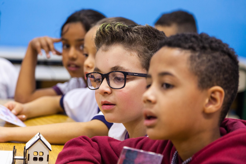 Em sala de aula, estudantes olham atentos para um dos lados da sala. Fim da descrição.