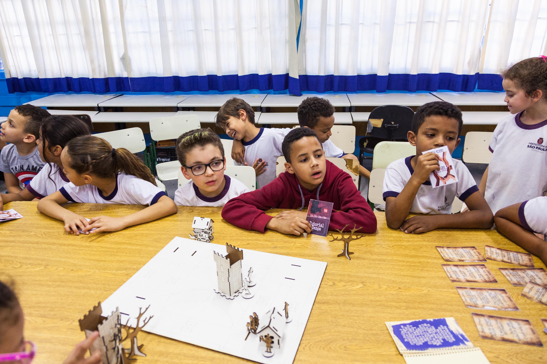 Em sala de aula, estudantes observam Tabuleiro de RPG depositado em cima de mesa. Fim da descrição.