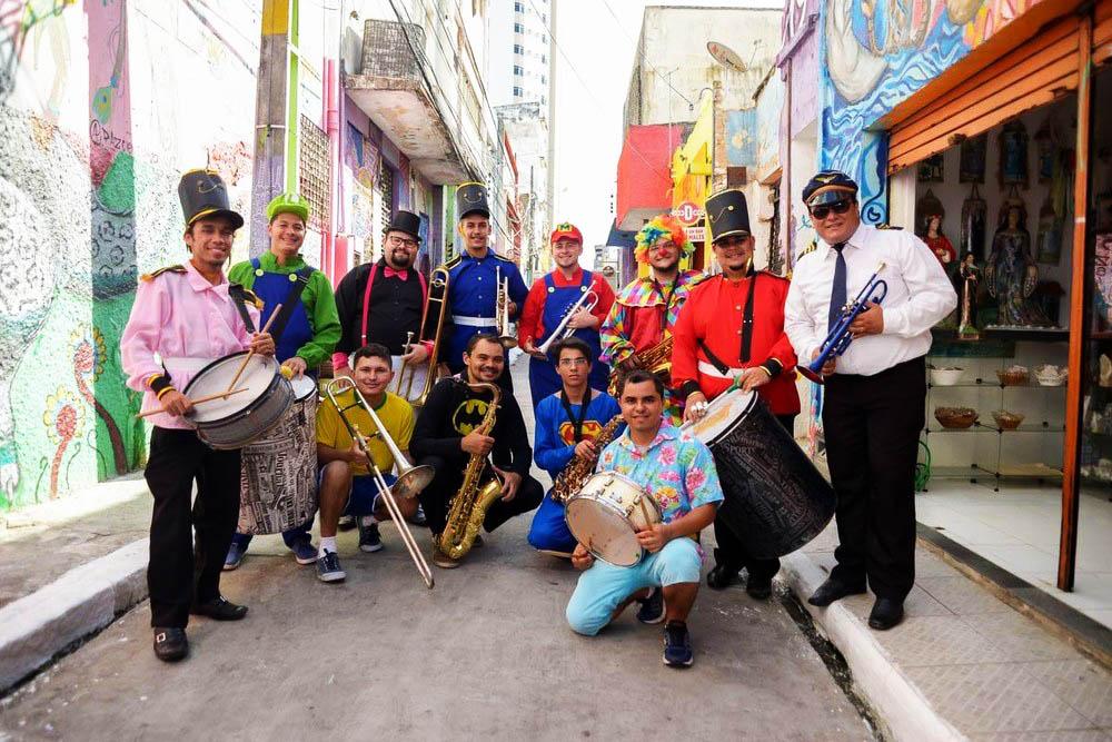Em rua colorida, diversas pessoas fantasiadas e carregando instrumentos musicais posam para foto sorridentes. Fim da descrição.