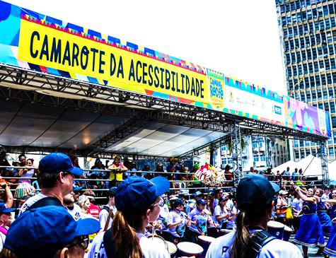 """Uma tenda no carnaval de rua, cheio de pessoas, com os dizeres: """"Camarote da Acessibilidade"""". Fim da descrição."""