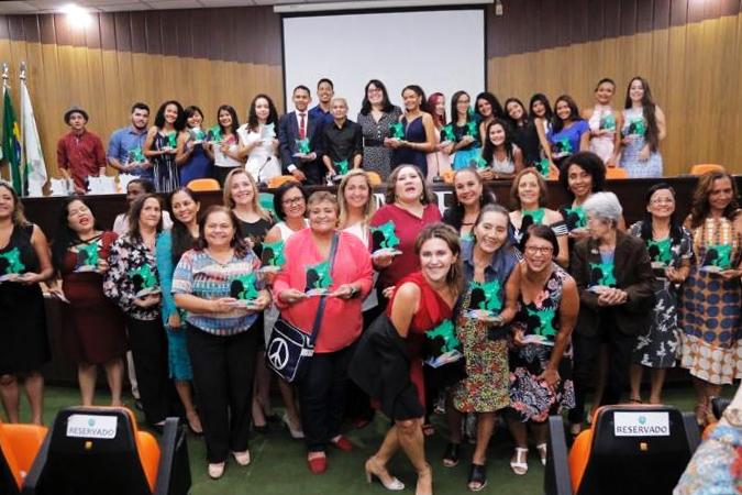 No Conselho Regional de Medicina de Roraima, mulheres entrevistadas e estudantes posam para foto em grupo sorridentes. Eles seguram nas mãos uma lembrança do trabalho realizado. Fim da descrição.