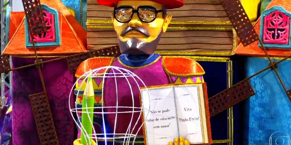 """Carro alegórico carnavalesco com boneco de Paulo Freire, que segura um lápis em uma mão e um livro em outro, com os dizeres: """"Não se pode falar de educação sem amor. Viva Paulo Freire!"""". Fim da descrição."""