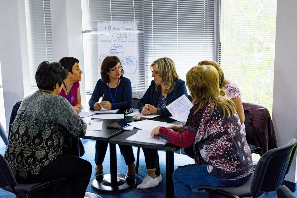 Educadoras conversam, sentadas ao redor de uma mesa. Fim da descrição.
