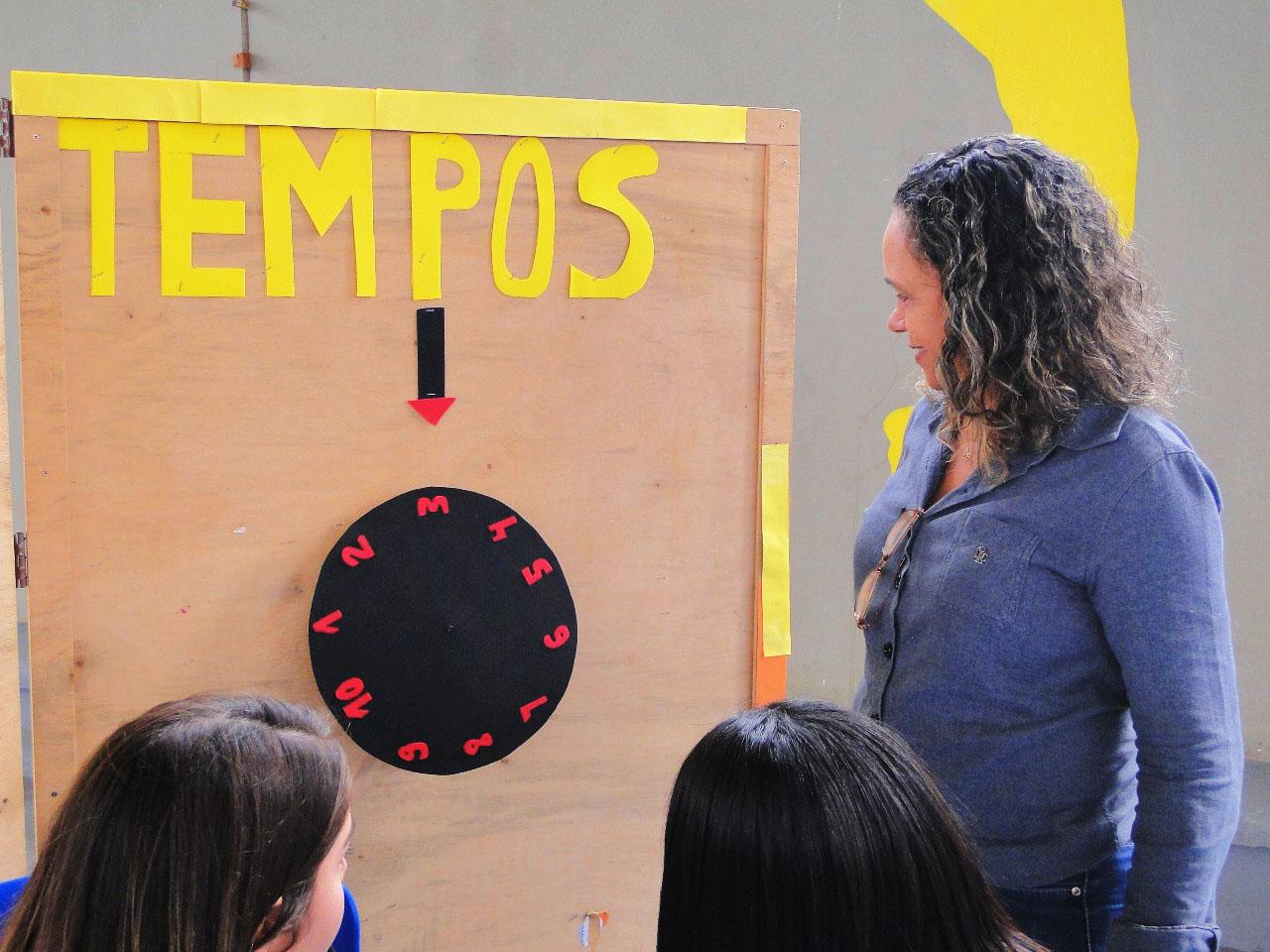 """Mulher de pé em frente a um quadro de madeira. No quadro, está colada a palavra """"tempos"""" em amarelo e há uma seta preta com a ponta vermelha apontando para baixo, onde está um relógio preto redondo com os números de 1 a 10 em vermelho deitados. Duas alunas sentadas e de costas olham o relógio. Fim da descrição."""