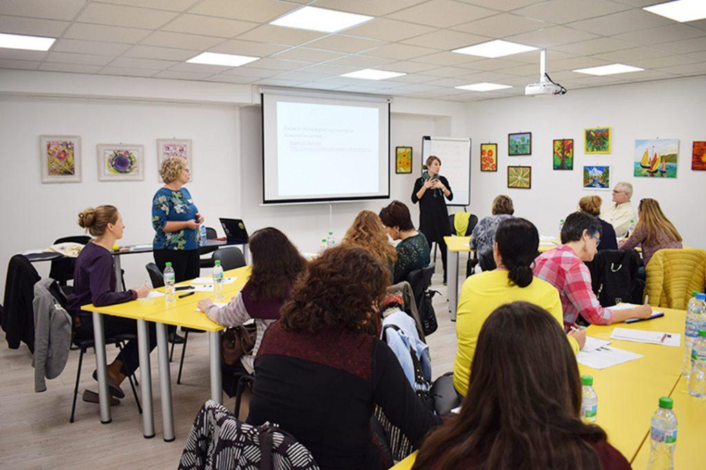 Em sala de aula, educadores assistem aula do programa One School For All sentados em cadeiras escolares. Fim da descrição.