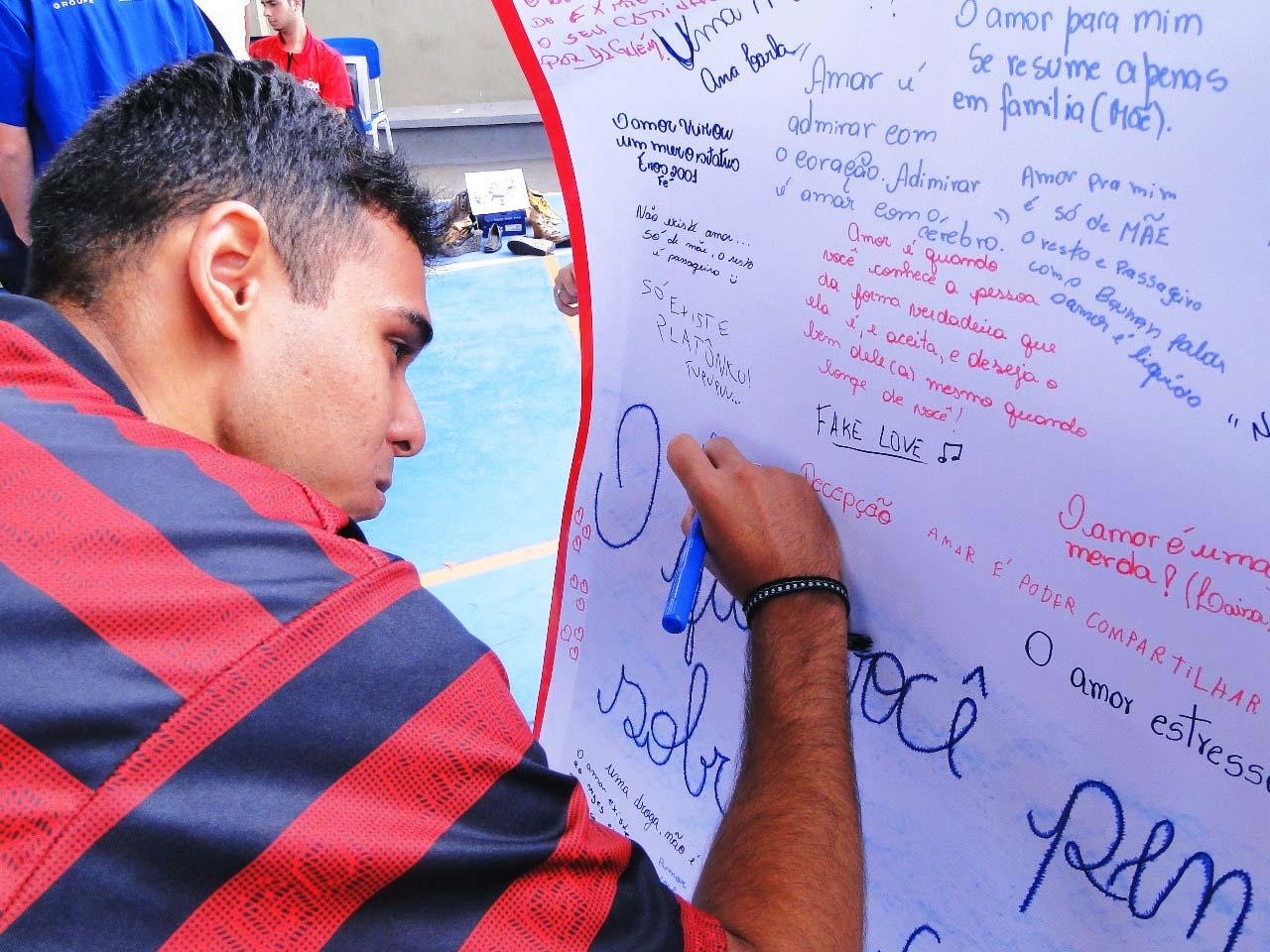Aluno, vestindo camiseta listrada em vermelho e azul, escreve de canetão em cartaz com várias frases de outros estudantes. Fim da descrição.