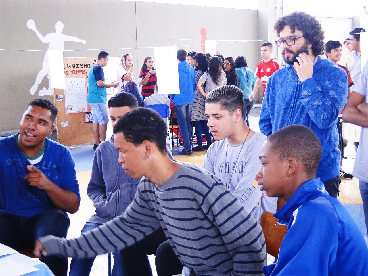 Em quadra escolar, seis alunos estão à frente da imagem, sentados e observando materiais que estão fora do quadro. Atrás, diversos estudantes em pé interagem com outra amostra do projeto. Fim da descrição.